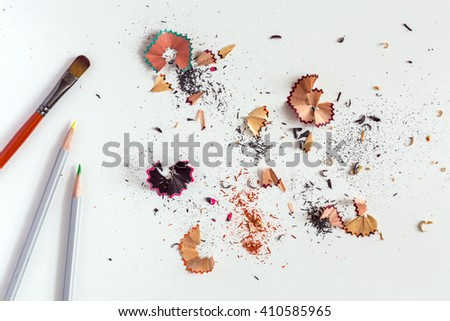 Creativity Concept Image of Brush color Pencils and shaped wood Chips and Shavings of sharpening a pencil on white Table - stock photo