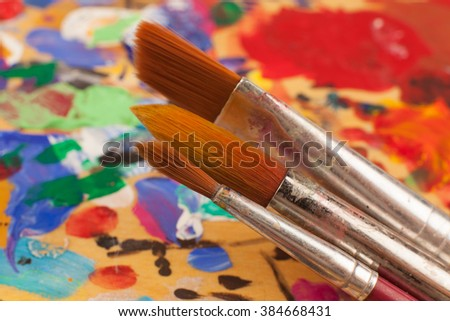 Creativity. Drawing. Brushes of different size and thickness against the multi-colored wooden palette