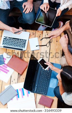Creativity in action. Top view of four young people working together while sitting at the wooden table - stock photo
