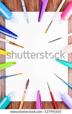Creativity ready. White sheet of paper spread out around the brushes, scissors and paints. - stock photo