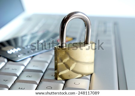 credit card and big lock on computer keyboard - stock photo