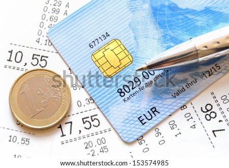 Credit Card and Euro coin on top of supermarket receipts - stock photo