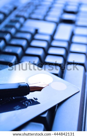 Credit card and fountain pen on a laptop. Selective focus, soft focus and shallow depth of fields - DOF - stock photo