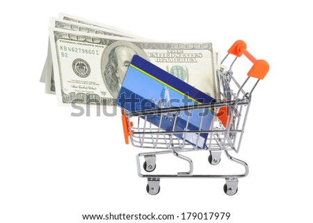 Credit card and money within shopping cart isolated on white background