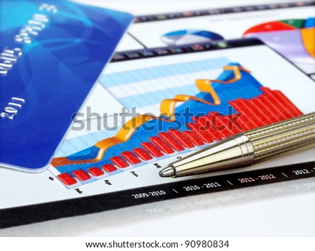 Credit card and pen on the charts - stock photo