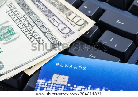 credit card and US dollar banknote on the computer keyboard - stock photo