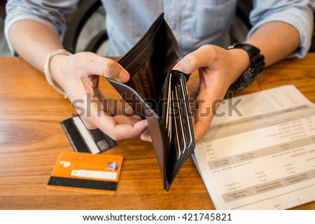 credit card debt - holding an empty wallet.  - stock photo