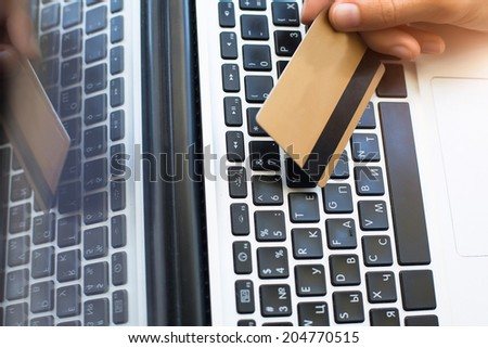 Credit card in a female hand, during shopping through Internet. - stock photo