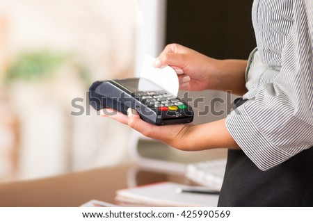 Credit card machine for fast payments, woman hands holding and swiping a white card - stock photo