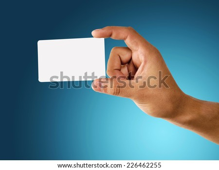 Credit card male hand holding on blue background - stock photo