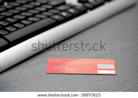 Credit card near computer keyboard  (fake number) - stock photo