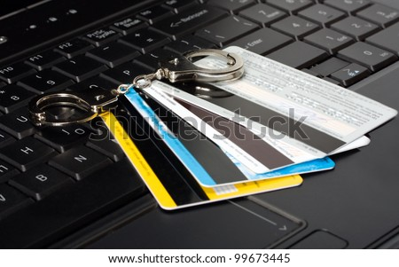 credit card of handcuffs on a computer keyboard - stock photo