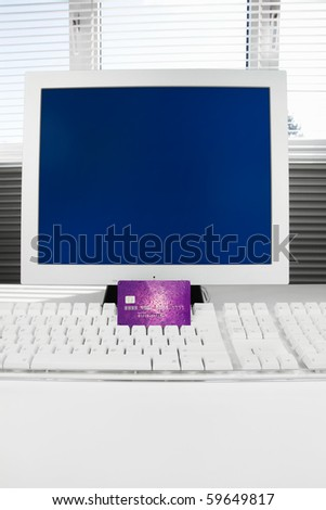 Credit card on a computer with a blank screen for copy space