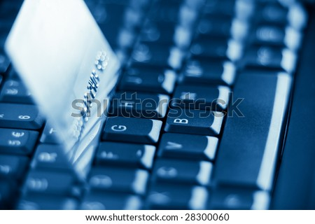 credit card on keyboard with shallow depth of field - blue toned