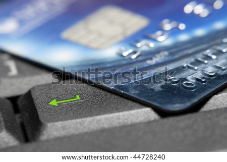Credit card on laptop buttons - stock photo