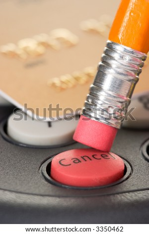 Credit card on pin pad card reader out of focus with attention on red cancel button pushed by pencil - stock photo
