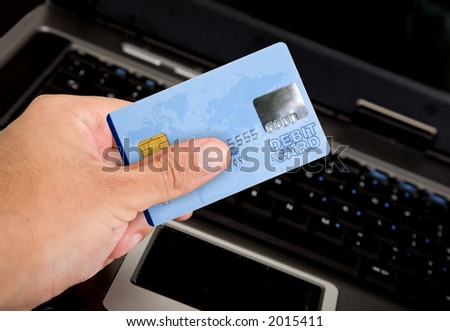 credit card over a computer keyboard held by hand - note the design of the card is my own