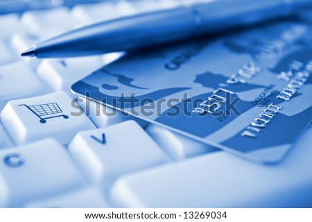 Credit card over a keyboard with a SHOPPING CART conceptual key - stock photo