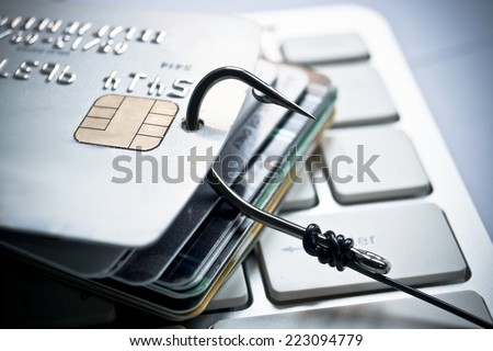 credit card phishing - piles of credit cards with a fish hook on computer keyboard - stock photo