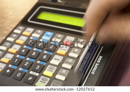 Credit card terminal swipe, hand in motion, DOF focus on stripe side - stock photo