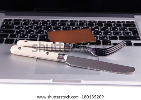 Credit card with fork and knife on computer keyboard close up - stock photo