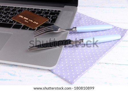 Credit card with fork and knife on computer keyboard on table close up - stock photo