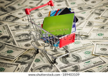 Credit card within shopping cart. Dollar background - stock photo