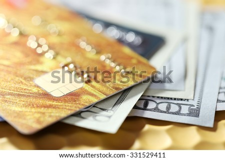 Credit cards and dollars on golden background - stock photo