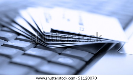 Credit cards and laptop. Shallow DOF - stock photo