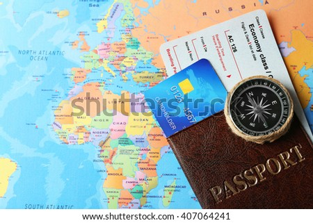 Credit cards with passport and tickets for vacations on the world map background - stock photo