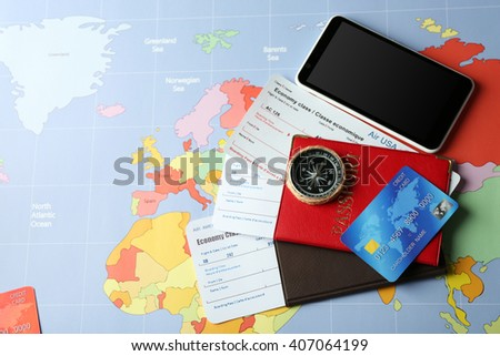 Credit cards with passports and tickets for vacations on the world map background - stock photo