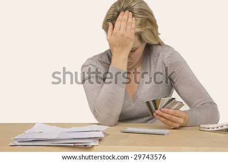 Credit Crisis - woman holding credit cards witting at desk with bills - stock photo