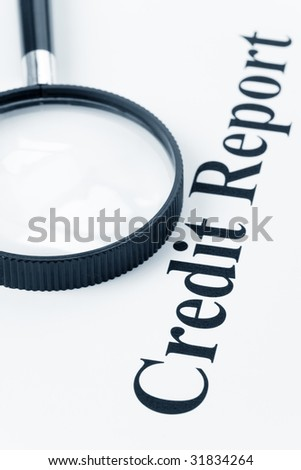 Credit Report and Magnifying Glass - stock photo