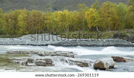 Creek, brook, river up North. Rocky canyon, stones and vegetation around the water. - stock photo