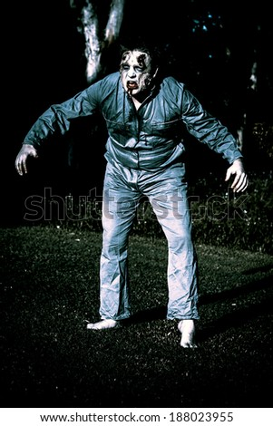 Creepy blue portrait of an evil dead horror zombie walking through graveyard during morning moonlight - stock photo