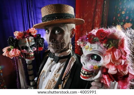 Creepy character in hay hat with a couple of hot skulls decorated with flowers. - stock photo