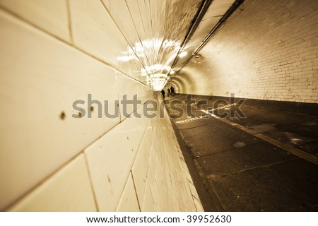 Creepy old tunnel below Thames river with blurred people crossing it. - stock photo
