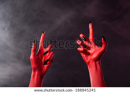 Creepy red devil hands with black sharp nails, Halloween theme   - stock photo