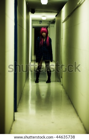 Creepy scene of a girl in dark corridor - stock photo
