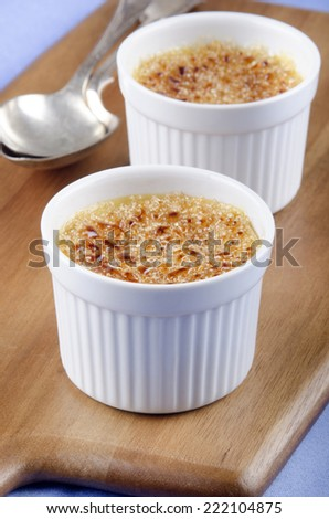 creme brulee and spoon on wooden board - stock photo