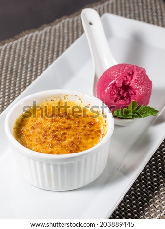 Creme brulee (cream brulee, burnt cream) with ice cream and mint - stock photo