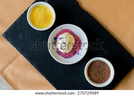 Creme brulee dessert with vanilla ice cream and berry leave on top, focus on ice cream - stock photo