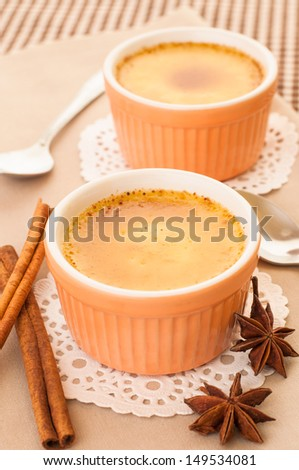 Creme brulee desserts with raw cinnamon and star aniseed. - stock photo