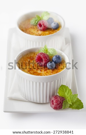 Creme brulee.French vanilla cream dessert with caramelised sugar on top.Isolated on white - stock photo