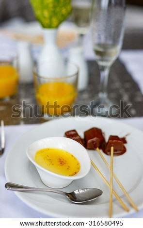 Creme brulee French vanilla cream dessert with caramelized sugar on top and fruits covered with chocolate. - stock photo
