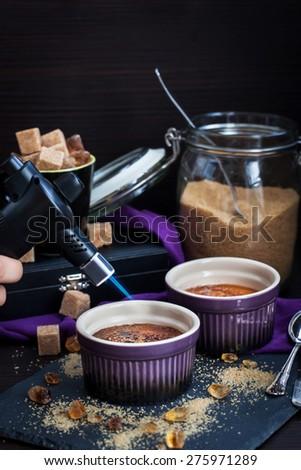 Creme brulee with gas burner caramelized, dark style photo  - stock photo