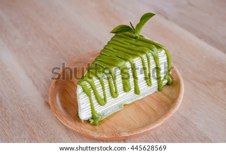 Crepe cake flavored green tea on a wooden plate. - stock photo