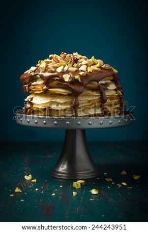 Crepe cake with custard cream and chocolate topping and nuts