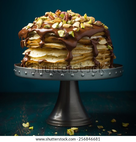 Crepe cake with custard cream, chocolate topping and nuts - stock photo