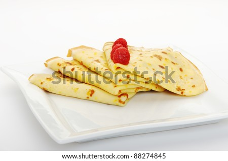 Crepe on a plate with a raspberry. A detailed photo fried thin pancake.Isolated on white